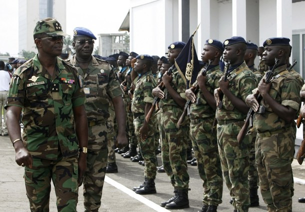Ivorian army chief General Mangou reviews his soldiers during a ceremony at the army's headquarters in Abidjan