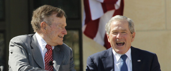 Former U.S. Presidents George H.W. Bush and George W. Bush shake hands at the dedication for the George W. Bush Presidential Center in Texas